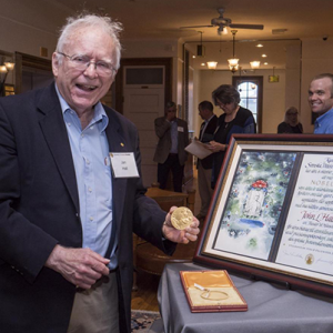 Photograph of Jan Hall with framed award.
